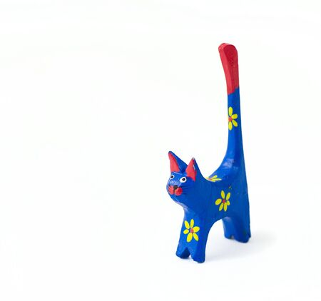 sculpture of wooden painted cat on the white isolated background, from face-front view photo