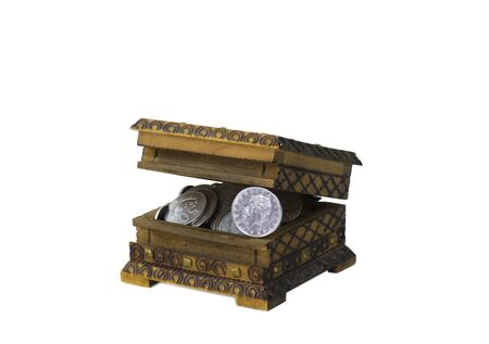 ajar wooden vintage moneybox filled with silver shine and dull coins