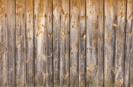 old vintage wooden wall of house in the village; arranged in stripes; untypical wood texture with nails, knots, moss Stock Photo