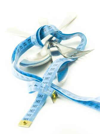 concept of limitation in food consumption; fork, knife and spoon tied together with measure tape Stock Photo