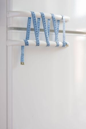 concept image of keep diet, white fridge doors are tied (knotted) with bow measure tape