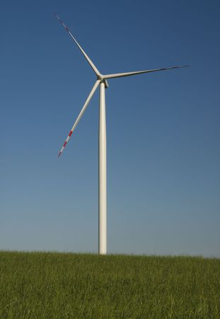 renewables: minimalistic view at windmill standing against blue sky Stock Photo