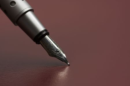 closeup of Silver fountain pen standing on the claret leather surface