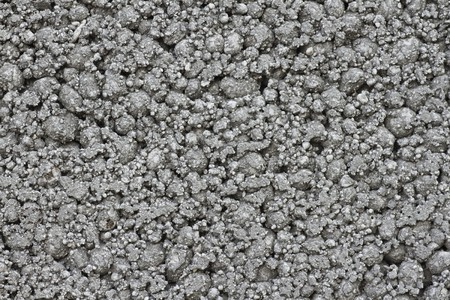 building material: close-up of grey coarse bumpy industrial concrete texture, building material