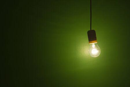 照らす: グランジ背景電球シャイニングと緑の背景に対してぶら下がって