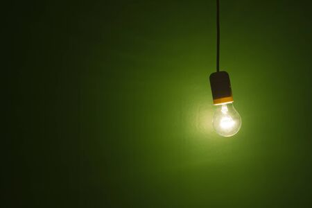 grunge background lightbulb shinning and hanging against green background photo