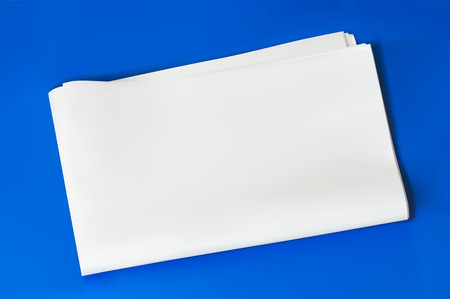 simulation: blank empty folded newspaper isolated on blue background with shadow