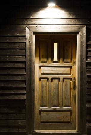 night scene with light on wooden door in board wall