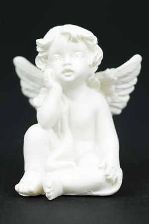 white gypsum angle figurine isolated on black background