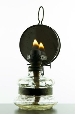 candil: vieja lámpara de aceite vendimia con el fuego aislado en fondo blanco