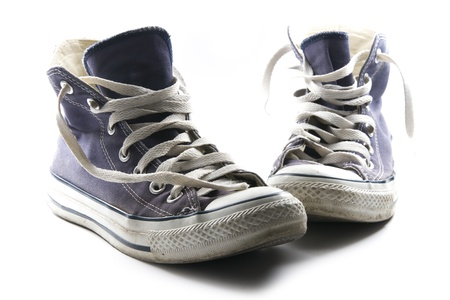 old worn-out dark blue sneakers isolated on white background photo