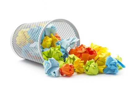 isolated tumbled office wastepaper basket with colourful crumbled paper ball Stock Photo