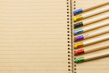 full-frame image of group of pencil with various colours rubber laying on spiral isolated photo