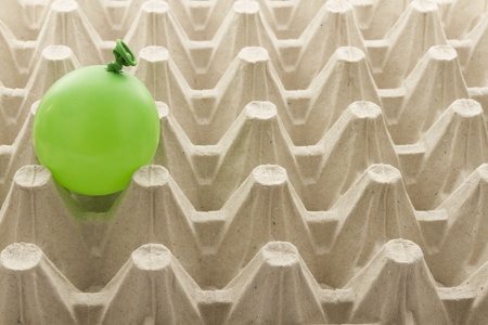 fragility: single balloon in egg cardboard container, concept of fragility Stock Photo