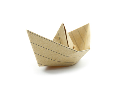 paper origami boat made with recycled paper isolated on white photo