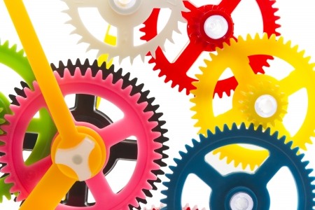 full-frame background multicolor clockwork cogs isolated on white with selective focus Stock Photo