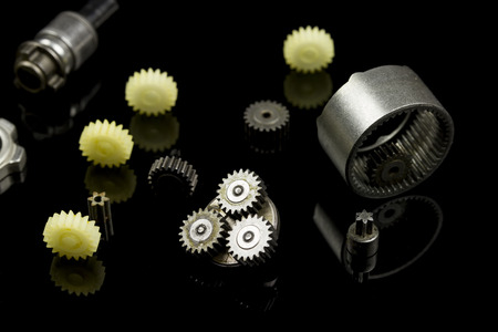 dismantled: dismantled gear box, element laying on black reflective background