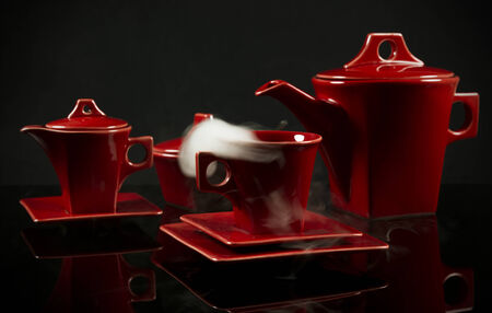 billow: red ceramic coffee (tea) crockery standing on black reflective background with steam