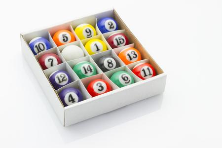 reflective background: sport billiard balls in box laying on white reflective background