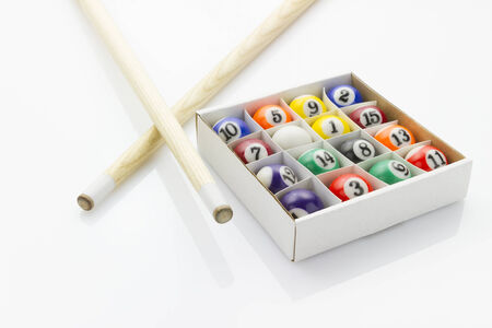 cues: sport billiard balls in box with cues laying on white reflective background Stock Photo