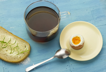 breakfast set with tea, bread and soft-boiled egg on blue painted wooden background photo