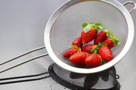 sift: fresh wet tasty strawberries in metal strainer on black reflective background Stock Photo