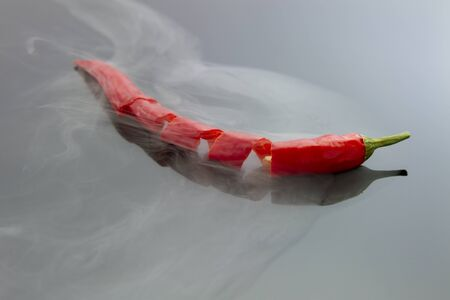 billow: spiral cutting red chili pepper with steam isolated on black reflective background Stock Photo
