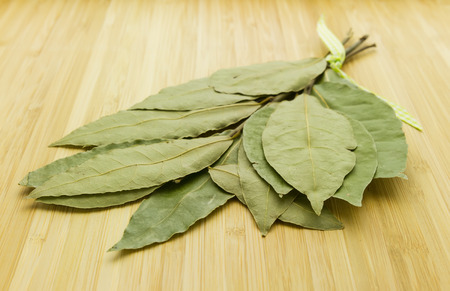 bunch of bay leaf herbs laying on wooden chopping board
