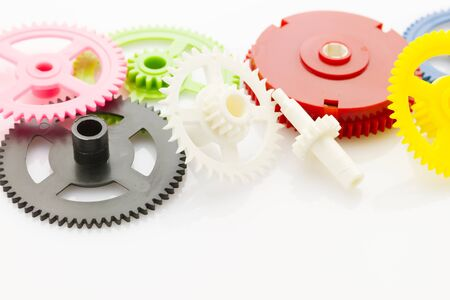 reflective background: group of plastic colorful clockwork gear on white reflective background