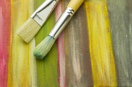 wood art: close up of pair paintbrushes laying on striped painted painting wallpaper Stock Photo