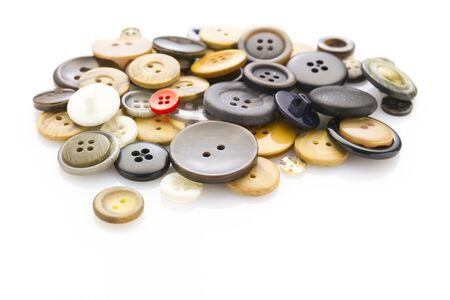 reflective background: collection of various buttons laying on white reflective background