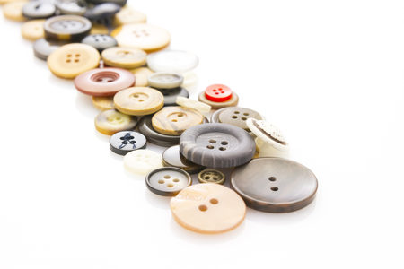 haberdashery: collection of various buttons laying on white reflective background