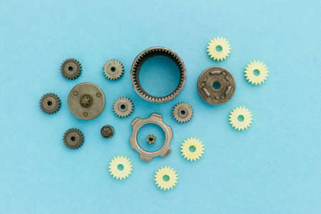 dismantled: metal and palstic gears of dismantled mechanism laying on blue background