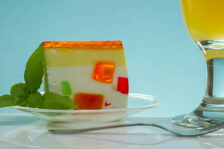 garnish: piece of jelly dessert with garnish on table with blue background Stock Photo