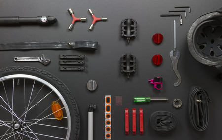 top view still life of bicycle parts, tools, and equipment on black grunge background