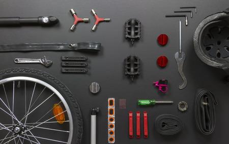 bicicleta: vista superior bodegón de piezas de bicicleta, herramientas y equipo en el fondo negro del grunge