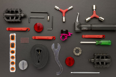 top view still life of bicycle parts, tools, and equipment on black grunge background photo