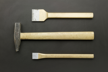 chisel: hammer and golden chisel laying on grunge blackboard Stock Photo