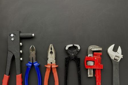 fix jaw: set of metal tools laying on grunge scratch blackboard