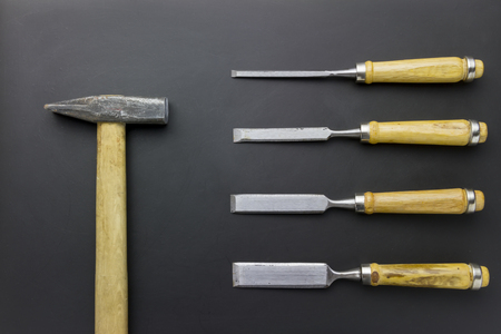 chisels: set of chisels and hammer on blackboard scratch grunge background Stock Photo