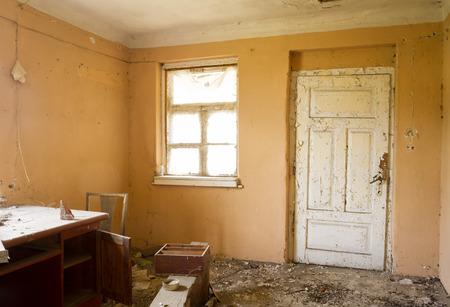 old home office: inside ruin, abandoned house with door and window in mess Stock Photo