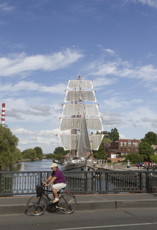 KLAIPEDA, LITHUANIA - 13 AUGUST 2015: Ship-restaurant Meridian is docked on the Danes river. View from bridge with cyclist.