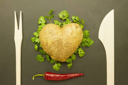 grunge cutlery: top view of heart-shaped potato on black grunge background with cutlery and decoration