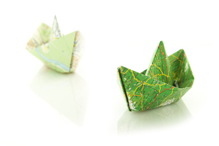 reflective: origami boats made with map isolated on white reflective  background