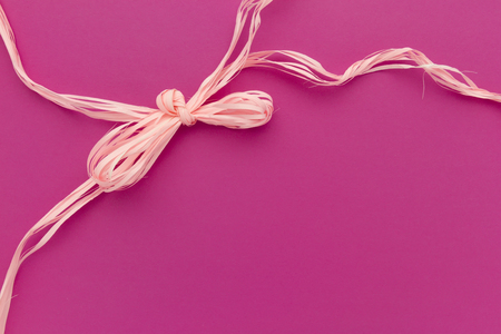pink greetings card with ribbon bow and copy space