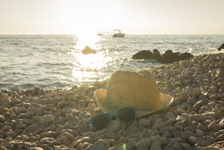 perspective view at hat and sunglasses lazing on pebble beach