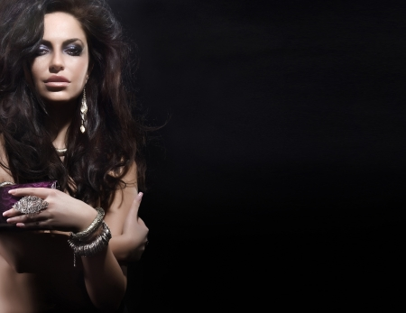 Portrait of beautiful woman with amazing hairstyle wearing jewellery  A lot of empty space  Black background