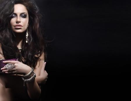 Retrato de la mujer hermosa con el peinado asombroso usar joyas Mucha fondo del espacio vacío Negro