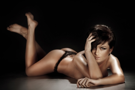 Sexy brunette woman lying and posing in lingerie on the floor  Black background Stock Photo