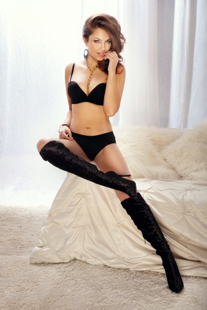 hand bra: Fashion shoot of sexy woman in black lingerie sitting on the white couch in the bright room  Stock Photo
